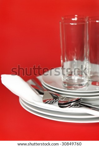 Pile of white plates, glasses with forks and spoons on silk napkin. Focus accent on front.  Red background - stock photo