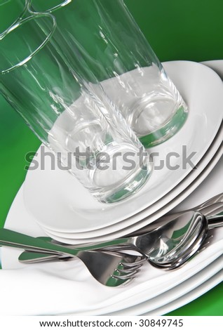 Pile of white plates, glasses with forks and spoons on silk napkin. Green background - stock photo