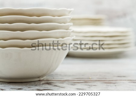 Pile of white porcelain plates lined on white wooden background - stock photo
