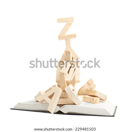 Pile of wooden letters over the opened book's surface, composition isolated over the white background - stock photo