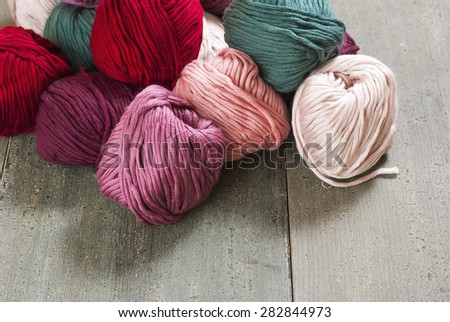 pile of woolen rolls on old wood table - stock photo