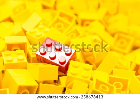Pile of yellow color building blocks with selective focus and highlight on one particular red block using available light. - stock photo