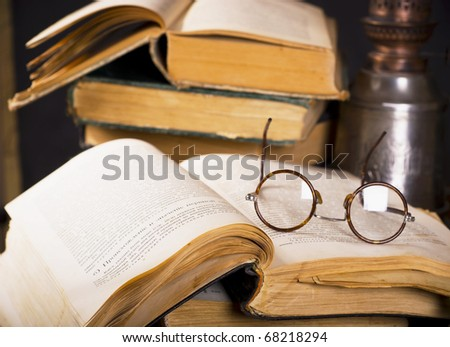 Pile old books and ancient lamp on dark and light background - stock photo
