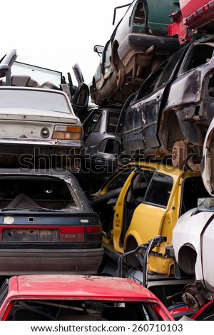 Piled up destroyed cars in the junkyard. - stock photo