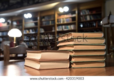 piles of books on table in library hall (Shallow depth of field) - stock photo