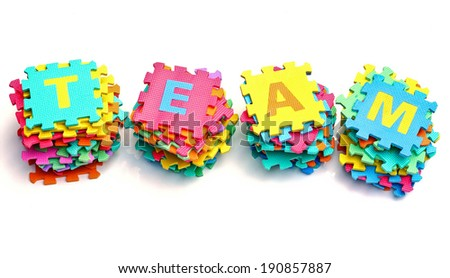 piles of colorful jigsaws arranged as the word team - stock photo
