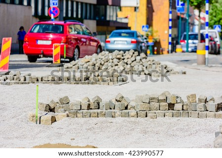 Piles of granite cubes or blocks are ready to be set in the road. Sand and gravel are spread out to support the stone. Traffic in background. - stock photo