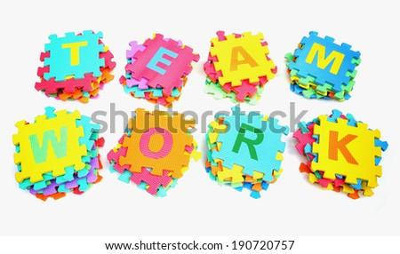 piles of jigsaw letter arranged as teamwork - stock photo