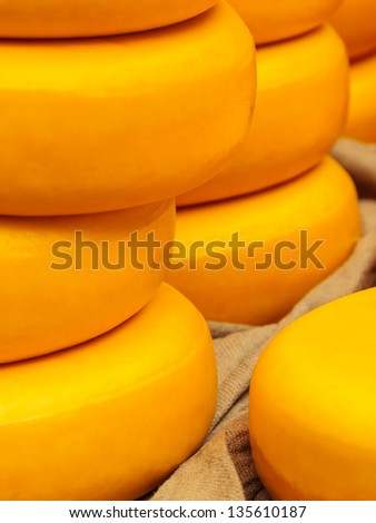 Piles of large round yellow Dutch cheese on a market - stock photo