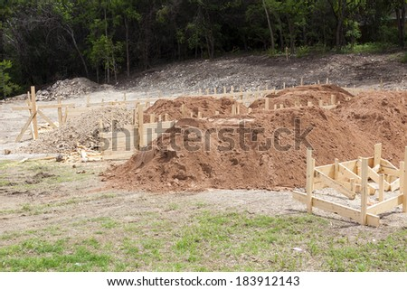 Piles of sand and gravel inside a wood frame mould at a home site under construction as preparations are made to pour a post tensioned steel concrete foundation. - stock photo