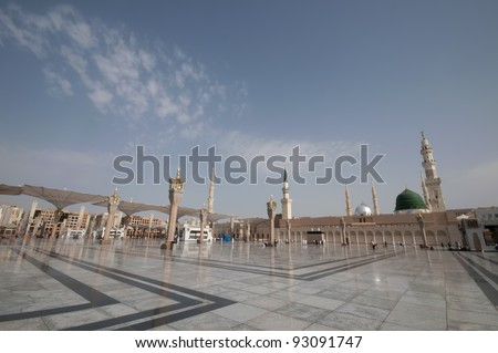 Pilgrims walk at the Nabawi Mosque compound  in Medina, Saudi Arabia. The mosque is the second holiest mosque in Islam. - stock photo