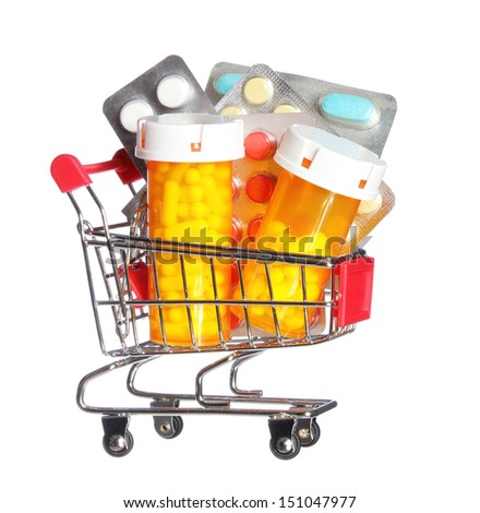 Pill bottle and pills in shopping cart isolated on white. Concept. Pharmacy - stock photo
