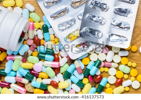 Pill bottle spilling pills and empty blister pack on to surface wooden background. View from the top use for background - stock photo