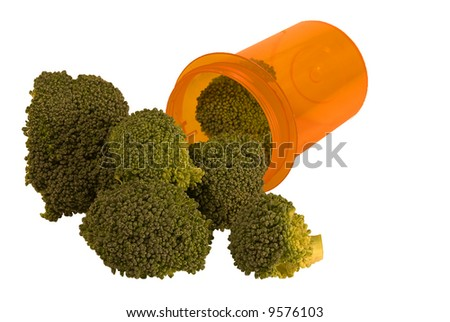 Pill bottle with broccoli in and around it - stock photo