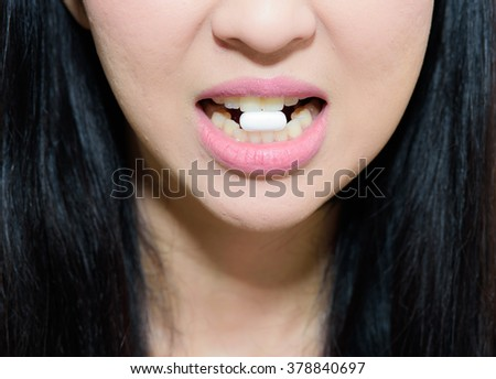 pill in young woman's mouth - stock photo