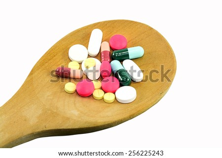 Pill on spoon isolated on white background - stock photo