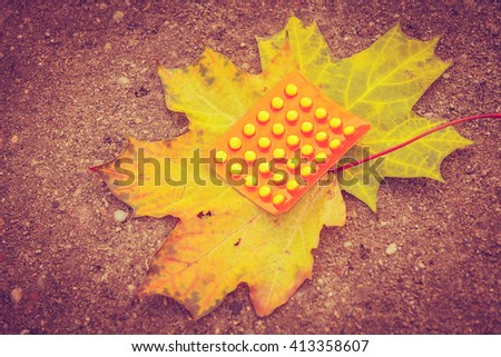 Pill package on leaf. Pack of pills lying on maple leaves. Nature vegetation health medicine concept.  - stock photo