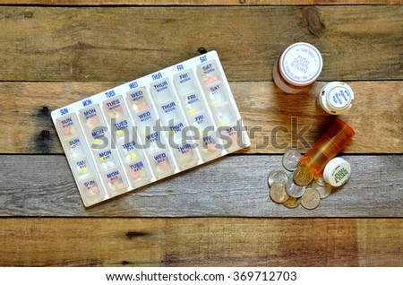Pillbox with medication, medical bottles filled with coins spilling out.  Concept of the high cost of medication, pharmaceuticals, drugs.  - stock photo