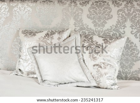 Pillows on a hotel bed. There are white satin pillows with silver pattern on it. Image taken as a closeup. - stock photo