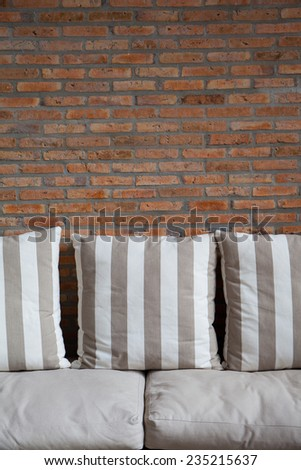 pillows on a sofa with brick wall in background - stock photo