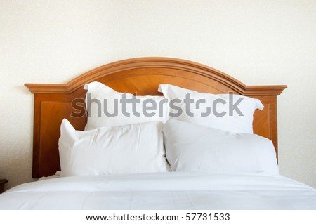 Pillows piled at the head of a large queen size double bed. - stock photo