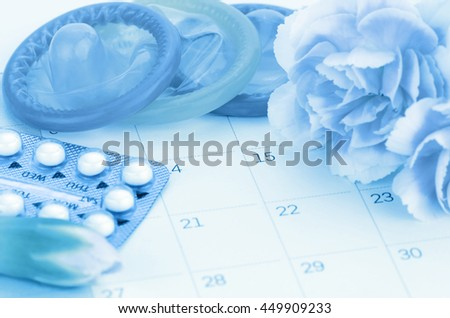 Pills and condom on calendar background with soft light in contraception education concept. - stock photo