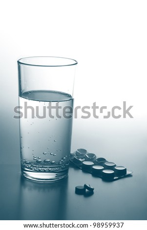 pills and glass of water. monochrome - stock photo