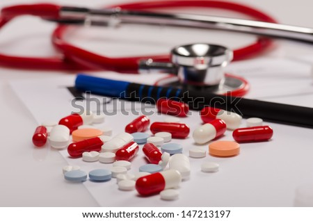 Pills and stethoscope scattered  on a prescription - stock photo