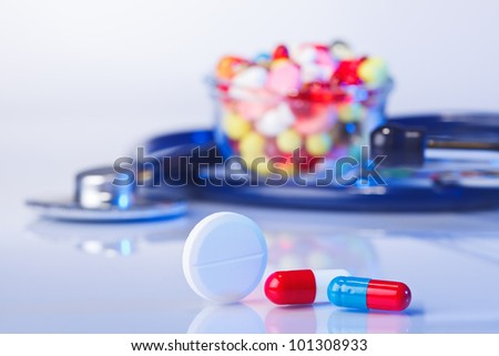 Pills and tablets macro still life on white blue, medical therapeutic concept - stock photo