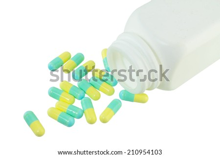 Pills Capsule, Herb capsule spilling out of a bottle on white background. - stock photo