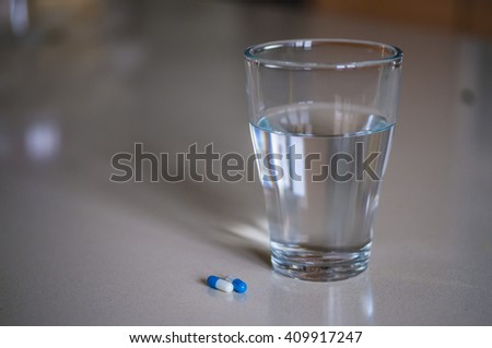 Pills capsules medicine and glass of water - stock photo