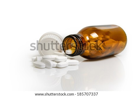 Pills from bottle isolated on white background - stock photo