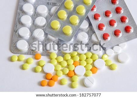Pills heap yellow orange white  red on  white background - stock photo