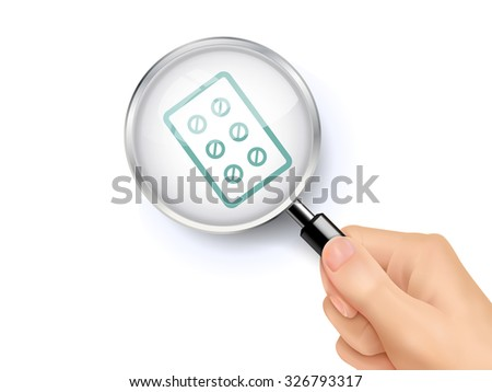 pills icon showing through magnifying glass held by hand  - stock photo