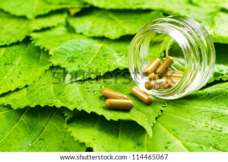 Pills in jar over green leaves. Healthy vitamin concept - stock photo