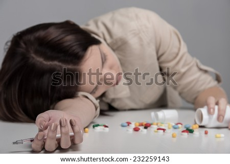 Pills lying on the table before suffering from the pain the young woman. - stock photo