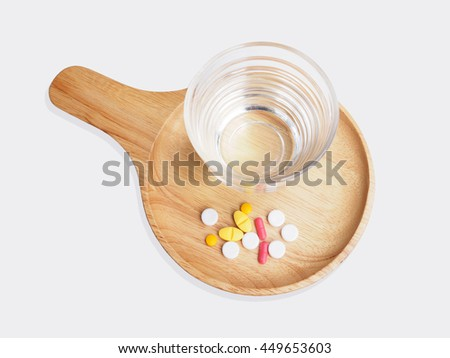 Pills medicine and glass of water on wooden tray isolated on white background - stock photo