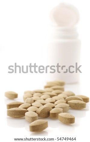 Pills of nutritional supplement and open container on white background. - stock photo