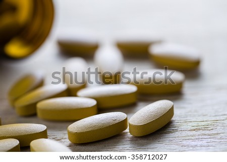 Pills of vitamin C spilled out open container on wood background. - stock photo