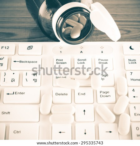pills on keyboard computer on wooden background concept technology addiction vintage style - stock photo