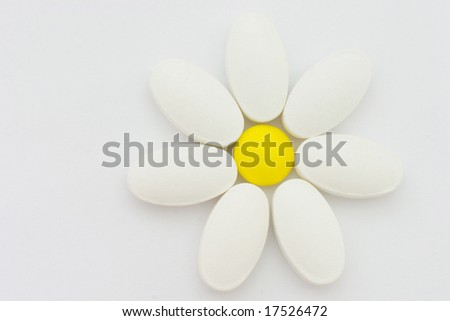 Pills, putted together in form of camomile flower. Symbol of nature, health and herbal medicines. - stock photo