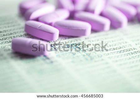 Pills scattered on paper with DNA data. Small depth of field. - stock photo