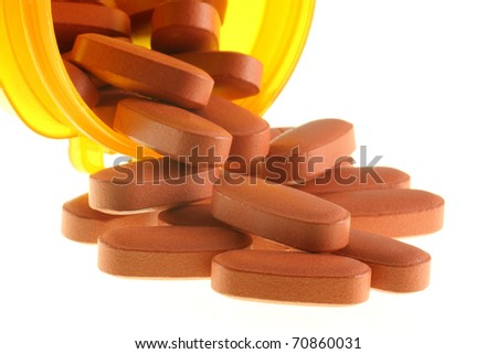 Pills spilling out of a bottle - stock photo