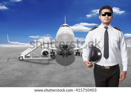 Pilot airplane in front of movable boarding ramp near the entrance to the passenger airplane - stock photo