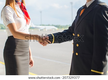 Pilot and stewardess shaking hands on airfield background. - stock photo