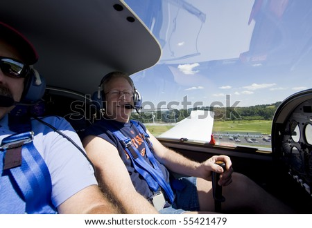 pilot flying small aircraft with view of sky and green fields - stock photo