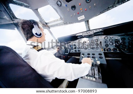 Pilot in an airplane cabin flying a plane - stock photo