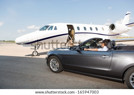 Pilot in convertible parked against private jet at airport terminal - stock photo