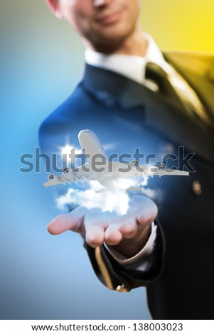 pilot in the form of extending a hand to a flying airplane with sky, clouds and sun - stock photo