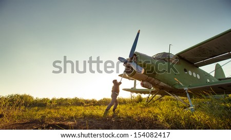 Pilot is starting engine of vintage plane. Rural background. - stock photo